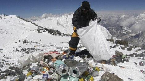 (FILES) This picture taken on May 23, 2010 shows a Nepalese sherpa collecting garbage, left by climbers, at an altitude of 8,000 metres during the Everest clean-up expedition at Mount Everest. Climbers scaling Mount Everest will have to bring back eight kilograms (17.6 pounds) of garbage under new rules designed to clean up the world's highest peak, a Nepalese official said March 3, 2014. AFP PHOTO/Namgyal SHERPA/FILES